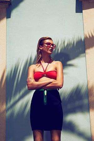 Swimming Pool Fashion: Model wearing red bikini top and black skirt