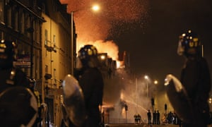 Riot police watch a fire burn in Croydon