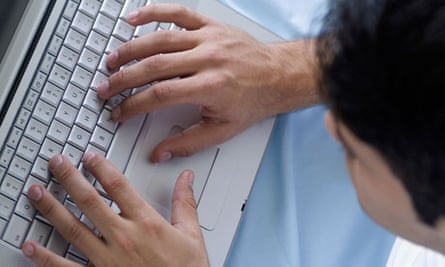 Young man typing on a laptop computer keyboard