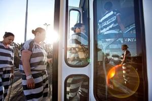 All-female chain gang: All-female chain gang board a bus en route to a highway roadside