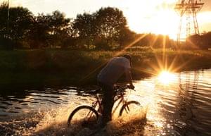 UK Flooding: Hebburn, Tyne and Wear: A man cycles through floodwater on Thursday evening