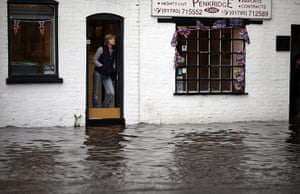 UK Flooding: Penkridge, Staffordshire: Shop workers look out at the flash flooding