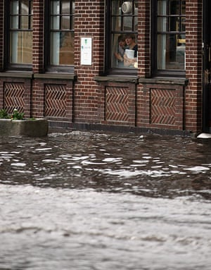 UK Flooding: Penkridge, Staffordshire: Bank workers look out on a rising flash flood