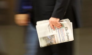 A man carries the Sydney Morning Herald, one of Fairfax Media's flagship titles