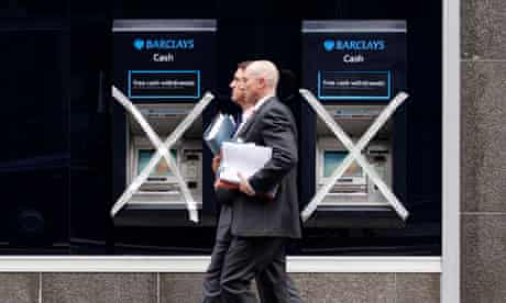 Two men pass a pair of closed cashpoints marked with masking tape in City of London