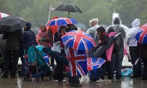 Jubilee pageant: Revellers hide from rain under Union Jack umbrellas