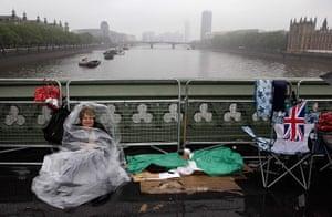 Jubilee pageant: A spectator waits on Westminster Bridge