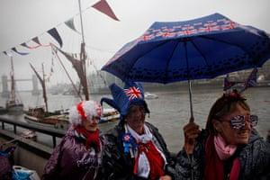 Jubilee pageant: People wait beneath an umbrella in the rain near Tower Bridge