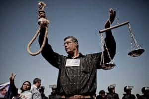 Mubarak trial: An anti Mubarak demonstrator holds a noose and justice scales