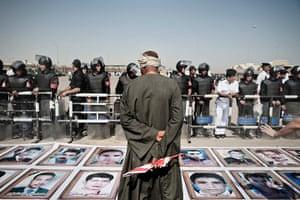 Mubarak trial: Anti Mubarak demonstrator stands in front of images of martyrs