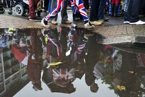 Jubilee pageant update: A woman wearing Union Jack leggins is reflected in a puddle Battersea Park