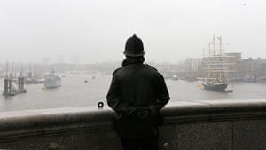 Jubilee pageant update: A policeman looks out over the River Thames from Tower Bridge