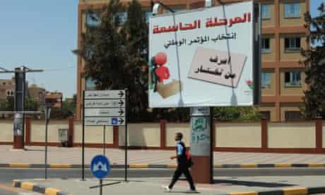 A student walks past an electoral billboard in Tripoli