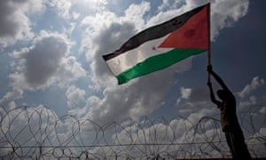 A Palestinian man waves his national flag in front of the separation wall