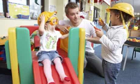Male teacher plays with kids at kindergarten