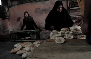 Gaza life: A woman buys freshly baked pita bread