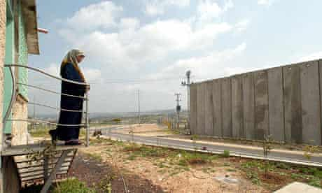 A Palestinian woman looks at the Israeli 'security fence'