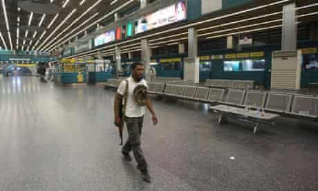 An armed militia member walks in a deserted terminal building at Tripoli international airport