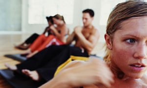 Young men and a woman doing fitness workout in a gym