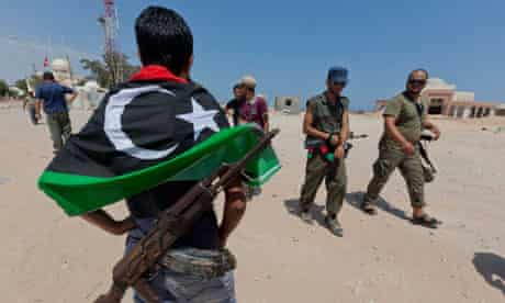 Rebel fighter in jeans with gun and new Libyan flag hung over shoulders watches his comrades