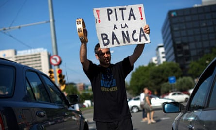 A demonstrator holds up a placard outside the La Caixa bank in Barcelona