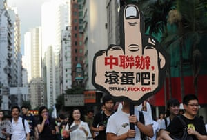 Hong Kong demonstrations: A man carries a placard saying 'Beijing liason office go to hell'