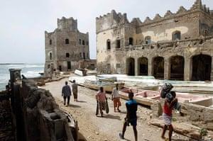 Somalia Goran Tomasevic: A man carrying fish walk past buildings destroyed during the warMogadishu