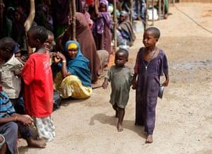 Somalia Goran Tomasevic: Boys arrive at an NGO compound before food distribution in Mogadishu