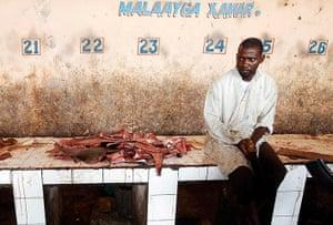 Somalia Goran Tomasevic: A man sells shark fins in a fish market in Mogadishu