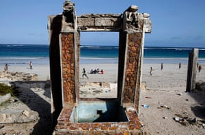 Somalia Goran Tomasevic: Men sit on a beach in front of a destroyed building in Mogadishu