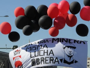 """Spanish coal miners hold ballons and a banner reading """"Miner's struggle = worker's struggle""""."""