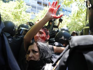 A woman covered in blood is surrounded by riot policemen during clashes between riot policemen and Spanish coal miners in Madrid, on July 11, 2012 during a miner's demonstration in protest at industry subsidy cuts that they say threaten their communities.