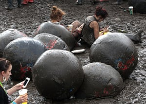 Wet festivals update: Two girls sit in the mud at Wireless Festival at Hyde Park