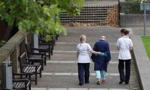 elderly patient with two nurses walking in hospital grounds