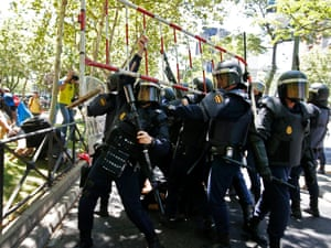 Riot police agents holding a barrier thrown by participants, during a miners' protests.