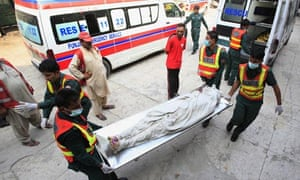 Rescuers carry out the body of a police cadet after a Pakistani Taliban attack on a house in Lahore