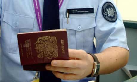 An immigration officer checks a passport at Terminal 1 at Heathrow airport