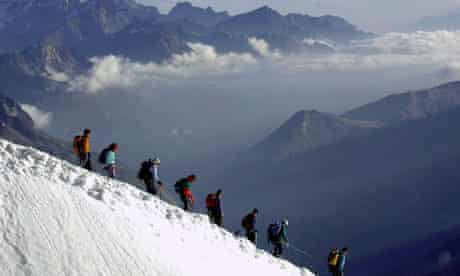 Climbers walk down the Aiguille du Midi, below Mont Blanc, in the French Alps