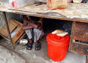 Mogadishu: A boy rests in his street shop in a fishermen port