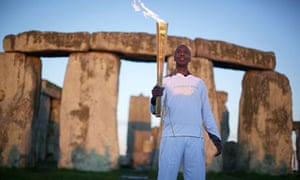 Former US Olympic athlete Michael Johnson poses for pictures with the Olympic torch at Stonehenge