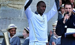 Former US Olympic athlete Michael Johnson with the Olympic torch at Salisbury Cathedral