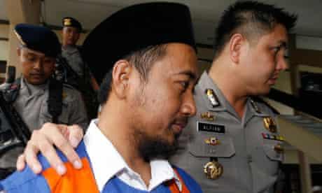Tajul Muluk is escorted into court in Sampang