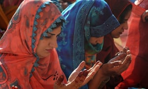 Pakistani Muslim women raise their hands