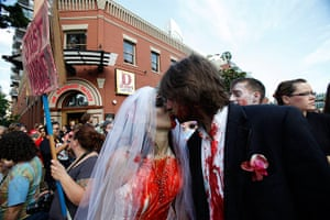 Comic-con: A couple dressed up as zombies kisses during a zombie walk