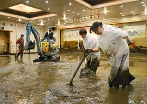 Floods in Japan: Workers shovel muddy water out of a banquet room of a hotel in Aso