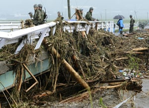 Floods in Japan: Ground Self-Defence Force personnel look at trees carried by floodwaters