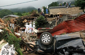 Floods in Japan: Police officers search for missing villagers after a mudslide in Minamiaso