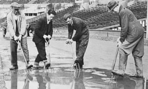 Workers drain the track at Wembley Stadium after  heavy rain during the London Olympics in 1948