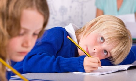 School boy thinking and writing in workbook