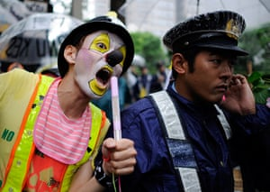 Japan nuclear protests: A protester with radioactivity make up performs next to a policeman
